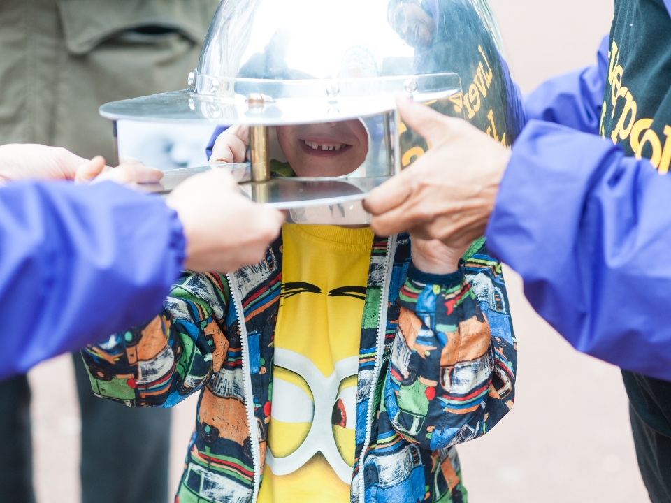 Volunteers help a young person try on on of 2015's Metaperceptual Helmets (c) Pete Carr. Thi simage is a detail of the original.