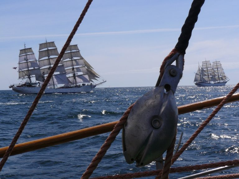 Close up of a pulley with tall ships racing in the distance