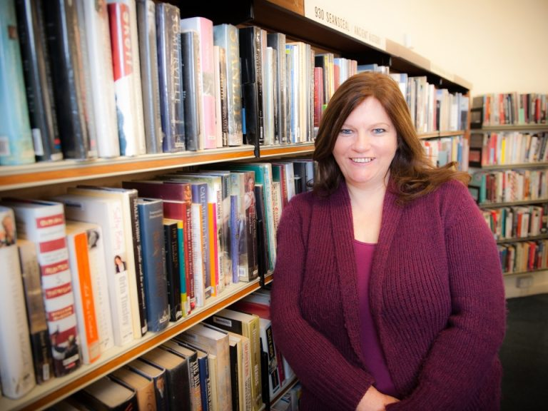 Carmel Kelly press shot - portrait in front of a series of bookshelves
