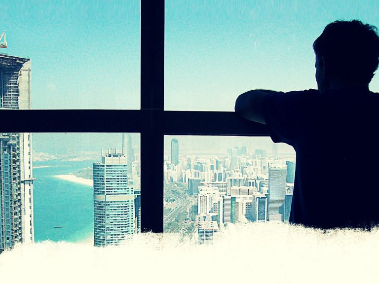 Male looks out at skyscrapers of a metropolis on a bight, cloud free day. Lead film image