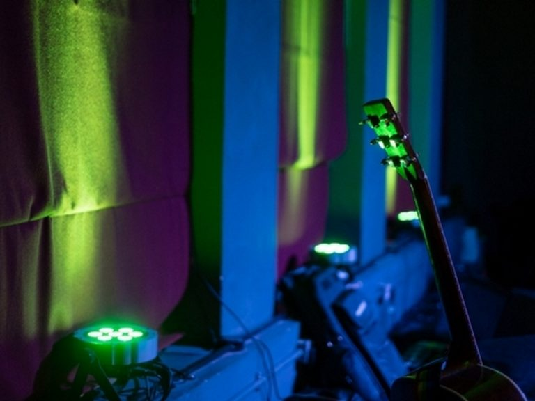 Colourfully lit white wall, with guitar, stand and LED lights (c) Peter Carr, 2015