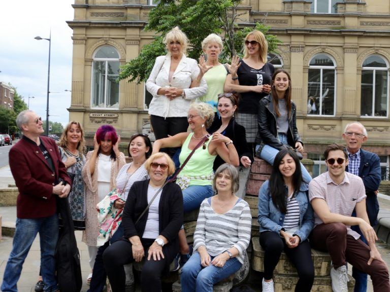 A Liverpool Music Tours group walk pauses o Hope Street at the Suitcase Monument