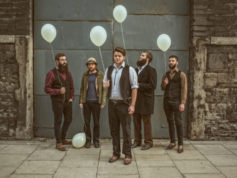 Press image of 5 of the eskies holding white ballons infront of a large industrial door