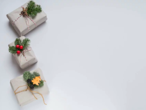Three Christmas presents in white paper, tied with spruce decorations.